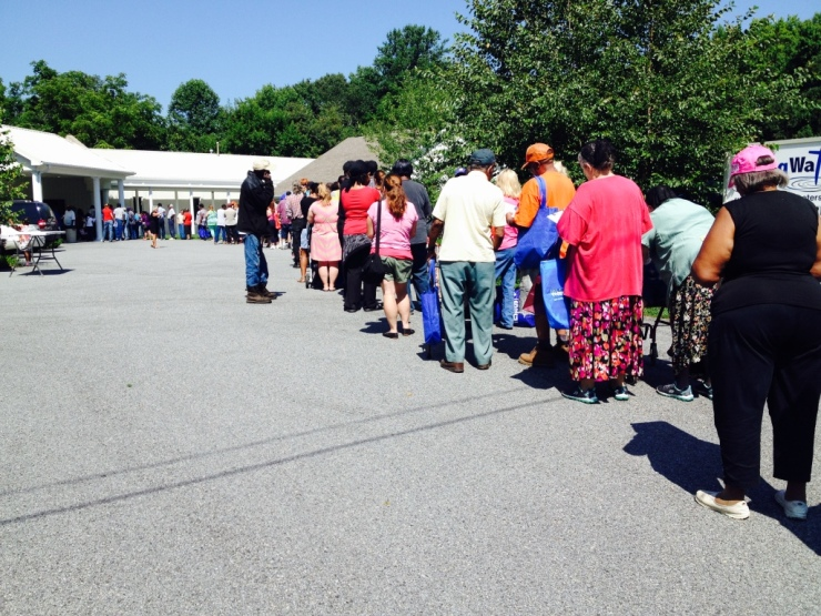 A long line of food insecure individuals patiently waiting on a hot day to get food at a MD Food Bank's partner agency in Denton